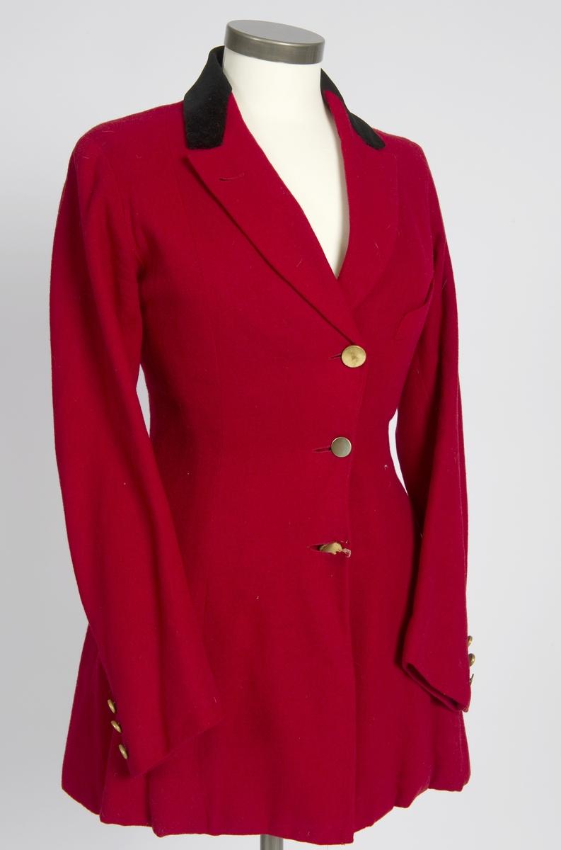 Rød ridejakke av ull, svart svart fløyel krage og gule metall knapper. Jakken er avkortet i nedkant, 16 cm er brettet in.
