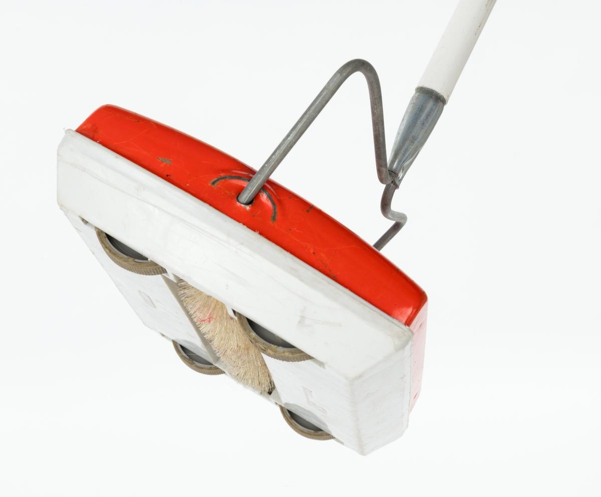 """Apparat til manuell børsting av tepper. Hvitt skaft (i tre deler) og selve apparatet i oransje-rød farge på oversiden med påskrift """"Pernille"""". På undersiden er fire hul i plast og en børste som roterer."""