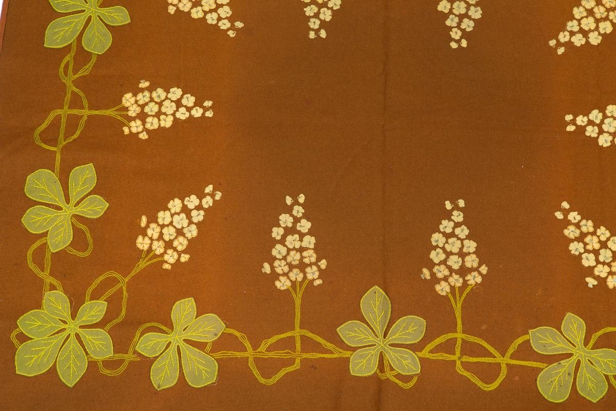 Rektangulær. Brunt toskaft ullstoff. Applikasjon og broderi. Dekoren, fliket blad og blomster, følger kanten og strekker seg mot midten