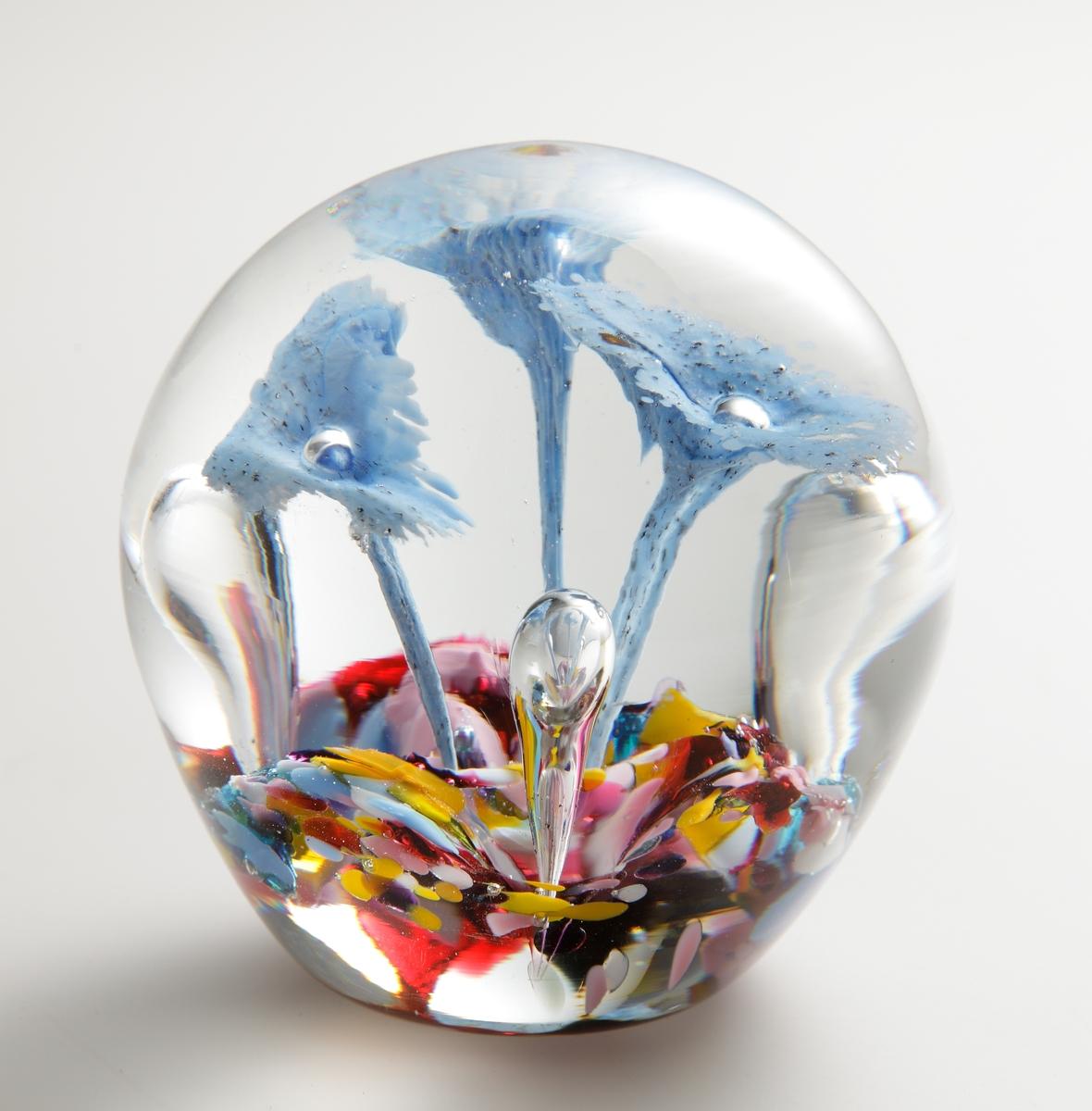 """Brevpress med botten av brokig glaskross i olika färger, ur vilken tre """"svampar"""" i blått reser sig, tillsammans med tre stående luftbubblor. Kompositionen är innesluten i ofärgat glas."""