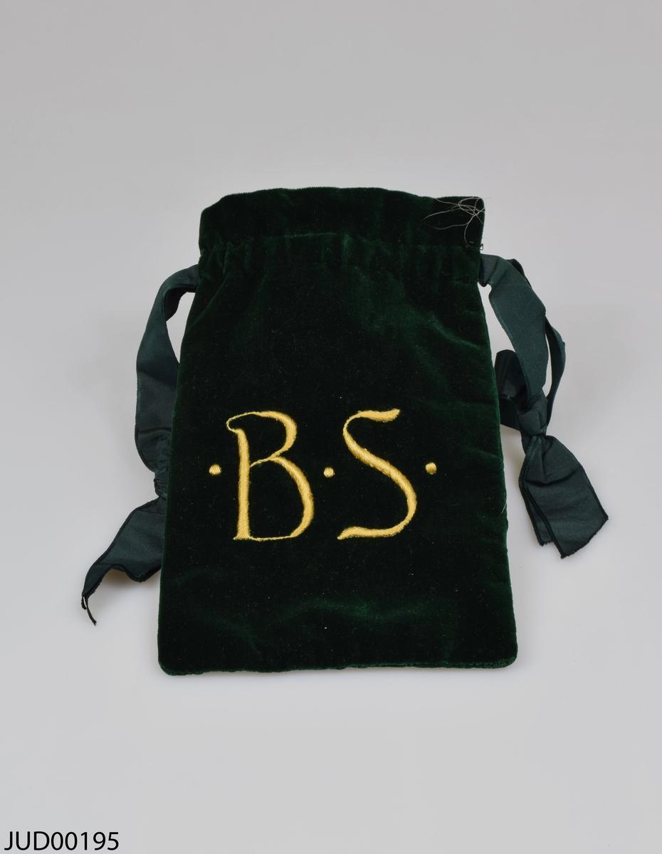 Påse tillverkat av grön sammet. Påsen är invändigt klädd med beige sidentyg dekorerat med blommor. Grönt sidenband i öppningen. Påsen är utvändigt dekorerad med guldfärgat broderi, i form av en davidsstjärna på ena sidan och initialerna B.S på andra sidan. I påsen ligger ett långt, gult brokadband.