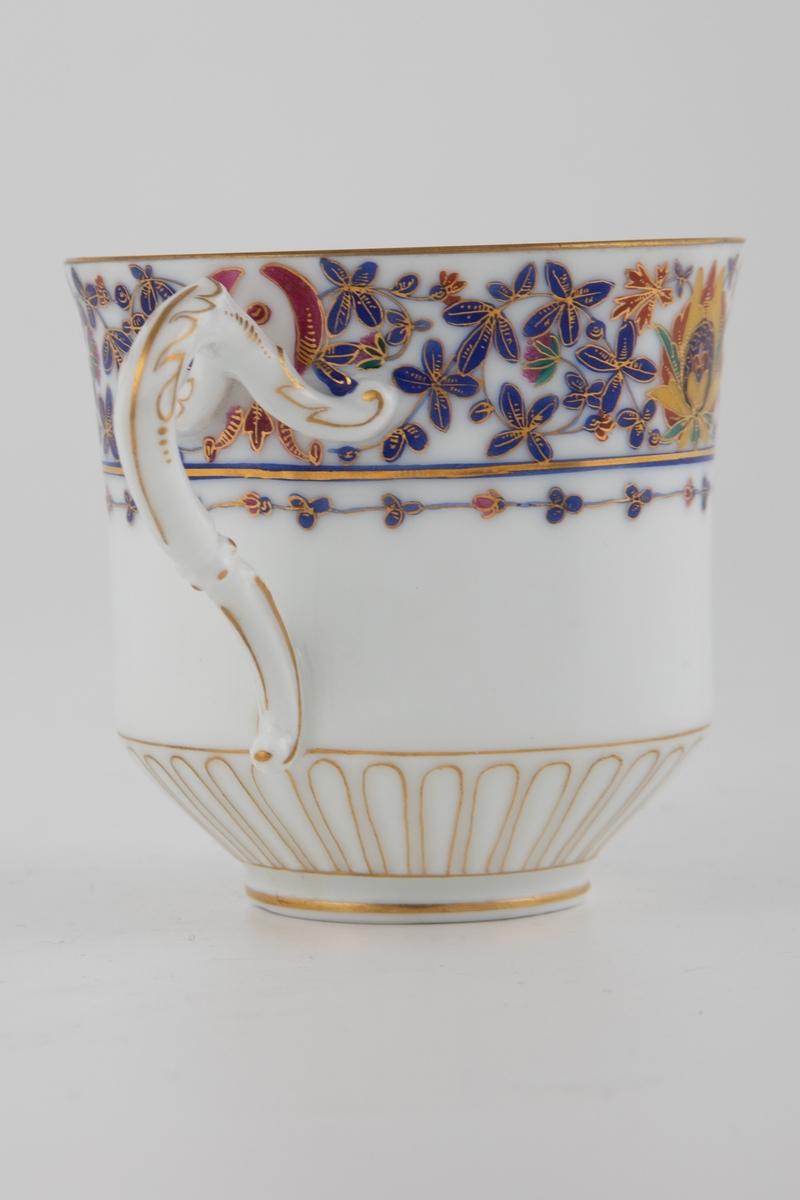 Tekopp med tilhørende skål i glasert porselen, dekorert med overglasurmaling og forgylling. Øverst på koppens ytterside er det fremstilt en blomsterbord med små rustrøde, rosa og blå blomster, som tidvis brytes opp av større rosetter med gule og grønne blad. Samtlige elementer har gullfargede konturlinjer. Koppens nedre del og hank er dekorert med forgylt detaljering. Innsiden er hvitfarget med en stilisert blomsterbord i blått og rosa nær munningsranden, samt i bunnen av koppen. Skålen gjenopptar koppens motiver og fargepalett, hvor blomsterborden løper langs kanten. Midten er dekorert med et blomsterornament, omkranset av et forgylt radiært mønster.
