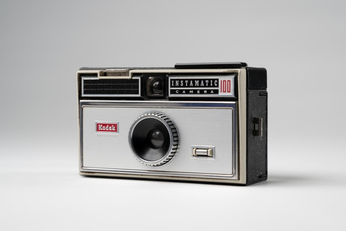 Kamera, Instamatic 100 av märket Kodak för filmkassetter. Av grå metall och svart konstläder. Öppning på baksidan, sikthål upptill i mitten fram och uttag för blixt på ovansidan.