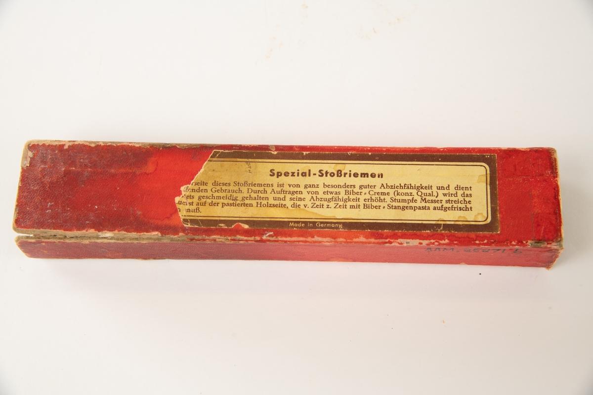 """a) strykestikke  b) eske til strykestikke  a) Selve strykestikken er trolig av bøk. På den ene siden er stiftet fast et stykke lær som hviler på rød filt. På motsatt side er pålimt et stykke bløtt, lyst løvtre, trolig osp. """"Juchten"""" betyr ruslær.  b) Den lengste innskriften er på esken. Esken er rød med gull varemerke med pålimt etikett på motsatt side."""