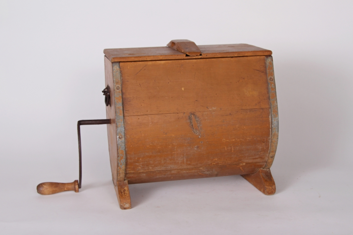 Tønneformet smørkinne med sveiv og lokk, montert på to små støtter.