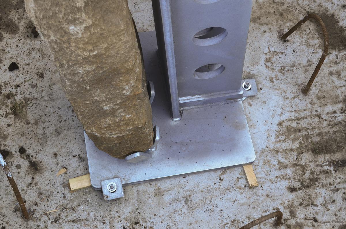 Remontering av Olavskrossen i Eivindvik. Kors og støttesøyle justert i vater og boltet til fundament.