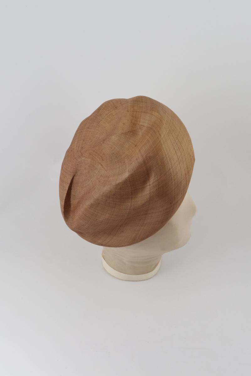 Brun hatt med brettet brem forann og påsydd remse med tvinnet tekstil ved bretten.