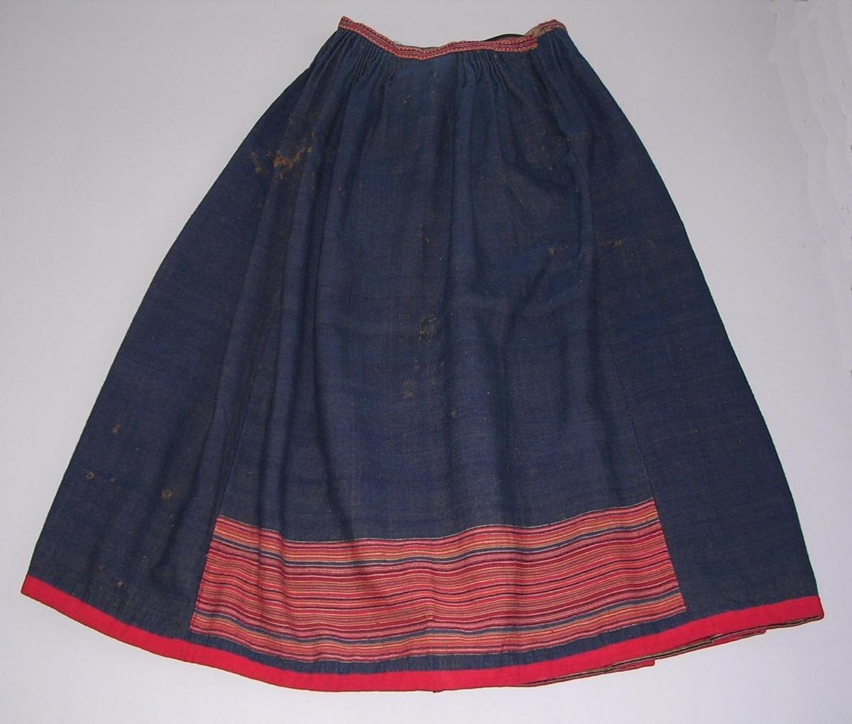 Mörkblå kjol från Toarps socken, Ås härad, Västergötland.  Varp brunt entrådigt lingarn och inslag blått entrådigt ullgarn. Inslagsrips. Handsydd. Kjolen är sydd av fyra våder, 64 cm breda. Framvåd mörkblå förutom ett 14 cm brett parti i nedre delen i rött, blått, grönt och vitt. Upptill tätt lagda veck, knäppta, utom 9 cm mitt fram. Linning, 2 cm brett handvävt  upphämtaband, i rött och mörkblått ullgarn samt blått, grön-beige och vitt bomullsgarn. Linningens insida ett likadant band. I vänster linningskant slutar bandet 5 cm från kanten,. Ett tuskaftsvävt naturfärgat ylletyg sytt på skrådden används till linning på dessa resterande cm.. Knäpps med hyska och hake i mässing Sprund till vänster om mitt våden,  infodring vitt tuskaftsvävt linneband, 8 mm brett. Nedtill 2 cm bred kantning med rött band, tuskaftsvävt, entrådigt ullgarn. Skoning 2,8 cm brett ripsband, rött, mörkblått och grönt ullgarn samt blått och gult bomullsgarn.