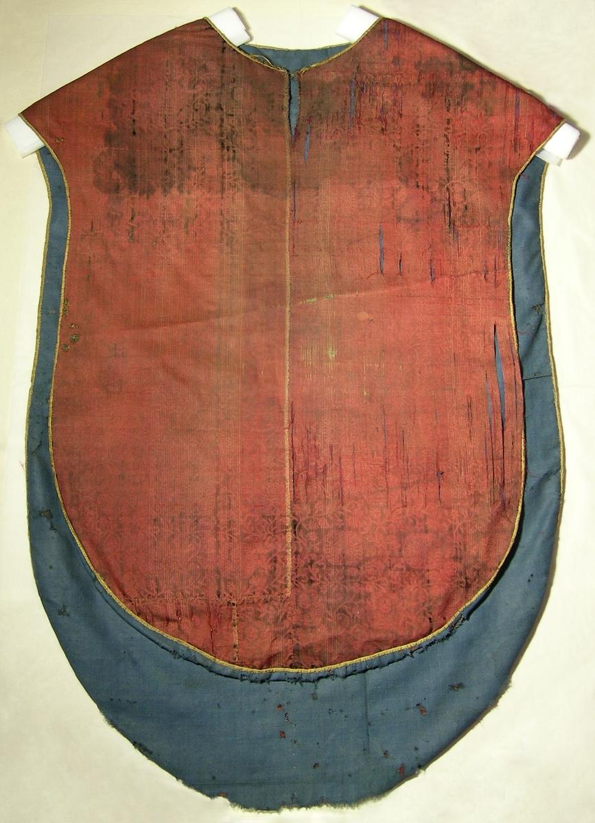 Mönstervävd sammet, röd och svart. Varp: rött silke (på vissa ställen gulvit tråd med jämna mellanrum) Polvarp: svart silke Inslag: gulvitt silke Blomrankor och bladmönster i röd 5-sk. satin mot botten i svart skuren sammet. Yllefoder i liksidig kypert (2/2), blått. Mässhaken har axelsöm och yttertyget är ihopsytt av flera stycken. Över axelsöm 12 mm bred spets av metalltråd (spunnet lan, silver). Runt kanten ca 8 mm brett fiskbensmönstrat silkeband, långrandigt i gulvitt och gult. I urringningen mitt fram 100 mm långt sprund med hyska och hake i gulmetall. Sprundet ej fållat, foder och yttertyg glest ihopkastat med grov brun tråd. På baksidan applicerat kors 385 x 300 mm av tredubbla rader spets i metalltråd (spunnet lan, silver), tillsammans 63 mm breda. Under korset 1654 applicerat med 5 mm brett band vävt av metalltråd (spunnet lan, silver).