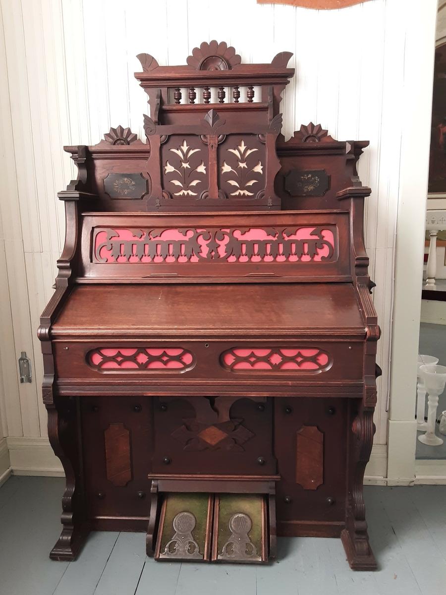 Orgelet er brunbeiset og lakkert. Orgelet består av et enkelt klaviatur og 11 registerknapper som kan trekkes ut/presses inn. Under klaviaturet er det to knesvellere og nederst to pedaler for trykkluft. Orgelet har en høy kasse med utskjæringer foret med lyserød tekstil for lydgjengivelse. Det samme gjelder sargen, altså kanten, under klaviaturet. Kassen over klaviaturet har en hyllerom med lokk som foldes ut, som har utskjæringer på forsiden. På hver side av dette hylleromet er det påmontert en liten sortmalt plate med malt dekor. Lokket til klaviaturet, løftes, opp og skyves inn. Orgelet har håndtak på begge sidene for transport.