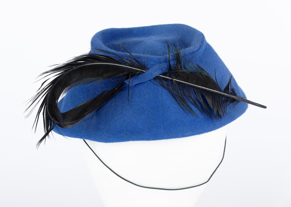 Filthatt med fjær, tilnærmet bøtteformet hattepull. Lang svart fjær. Fabrikk \ typemerke: La Familiare