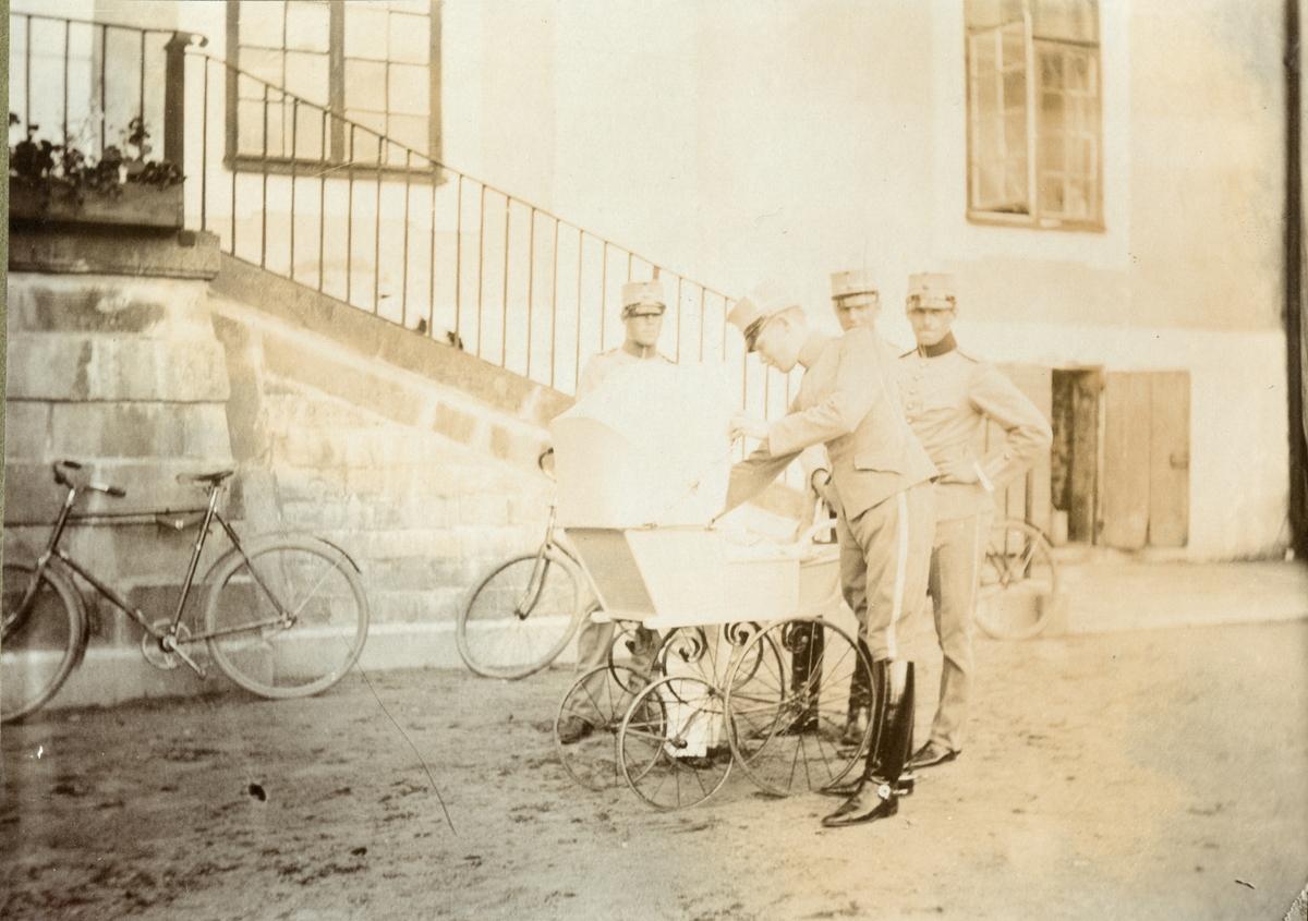 Grupp soldater och barnvagn framför byggnad.