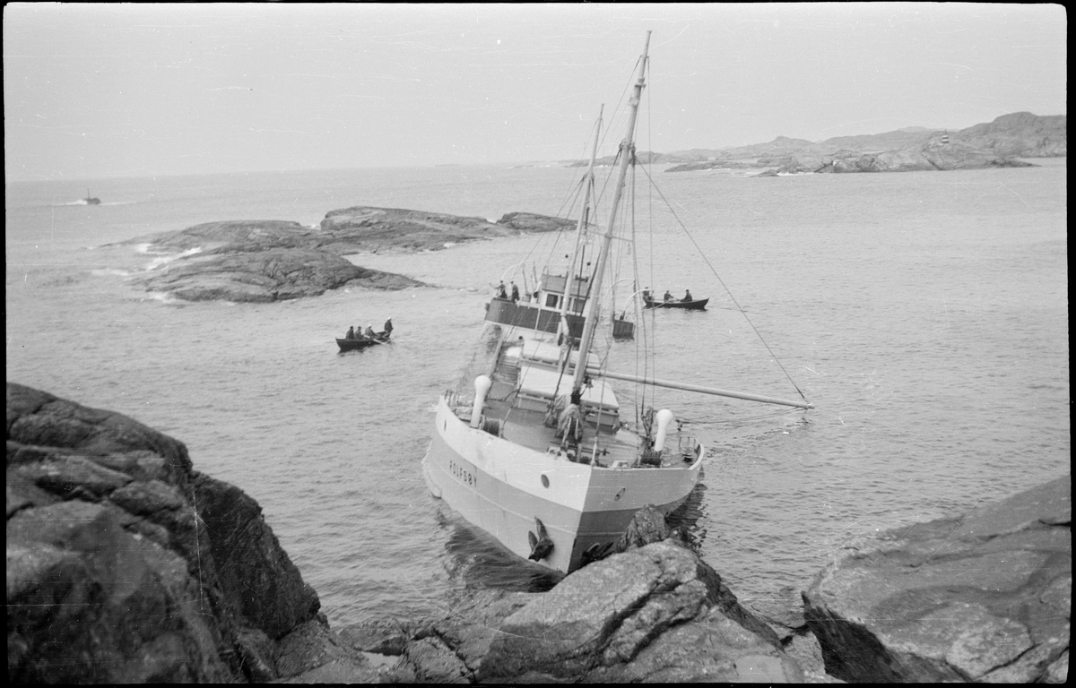 """Lasteskipet """"Rolfsøy"""" på grunn utenfor Egersund. Flere mindre båter er uten for å se og forankre skipet."""