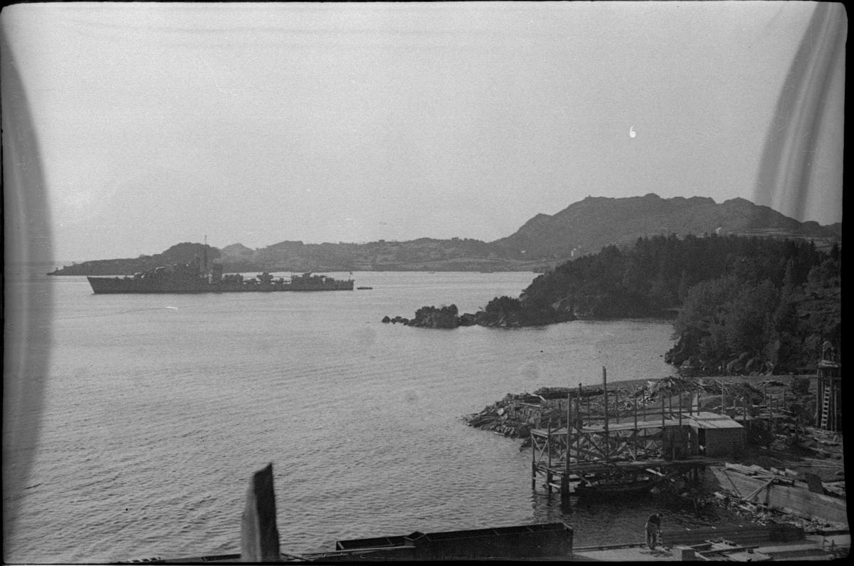 Fra Grønehaugen i Eigerøy og farvannene utenfor under byggingen av Sildoljefabrikken SILFAS. Det er en demning og steinbrudd. Det er også utsikt over fjorden mot Vågen ved Egersund og av noen marinefartøy på øvelse.
