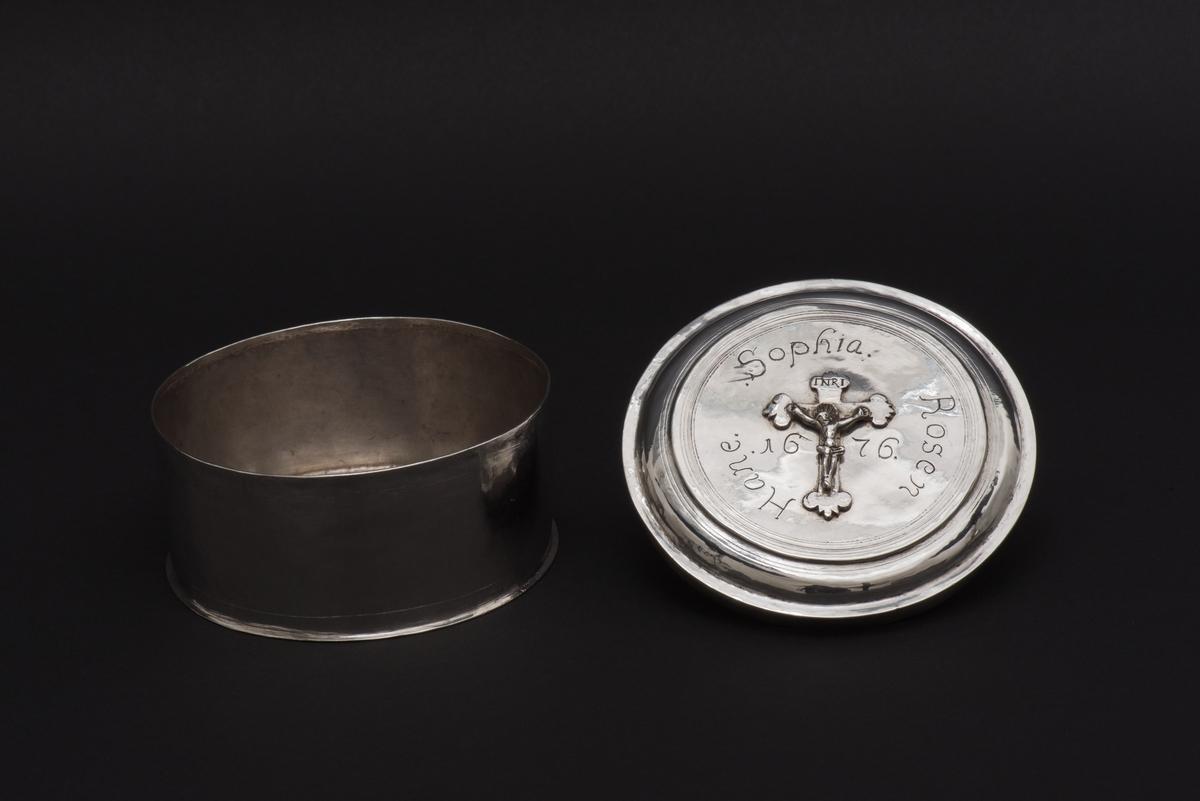"""Rund oblatask med lock av silver. Locket är dekorerat med ett krucifix och runt detta en inskription """"Sophia. Rosen. Hane. 1676. Två otydliga silverstämplar på askens undersida."""
