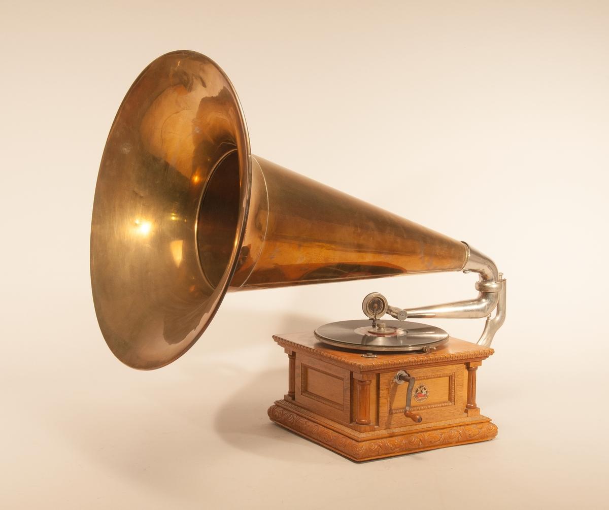 """Grammofon """"Die Stimme sienes Herrn"""", med stor tratt av mässing. Ljuddosa """"Exhibition Made in USA"""" tillverkningsnr. 49346. För komplettering av denna grammofon för långtidsdeposition i sept. 1962 har följande delar tagits från apparaten av samma modell: 1) Skruv med platta för att vridbart fästa tratten på grammofonen (från TM 22.901, defekt) 2) Skruv att hindra tratten att vrida ur knäskarvröret (från TM 22.901, defekt). 3) Skruv att klämma fast skivan på tallriken (utbytt mot bättre  förnicklad, TM 16.447). 4) Skruv för stiftfäste på ljuddosan (från ljuddosan TM 14.978). 5) Etikett av celluloid, varumärke skrivande amorin (från TM 16.447) 6) Snidad hörnpelare på lådan (från TM 22.901, defekt). 7) Den malätna duken på tallriken utbytt mot blågrönt kläde sept. 1962."""