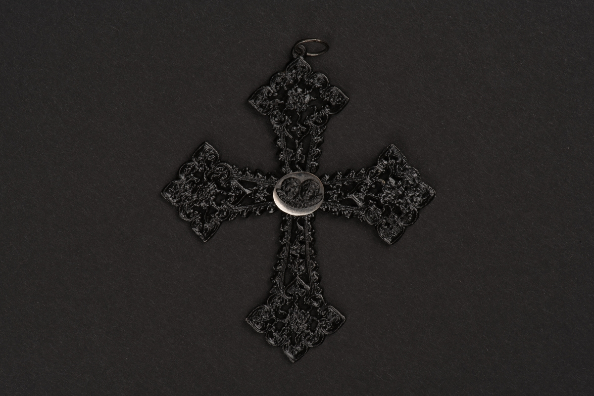 Hänge till halsband i form av ett kors. Korset är av utsirat svart gjutjärn med rombformade avslut i nygotisk stil. I mitten sitter en oval förnicklad platta med två änglahuvuden i gjutjärn.