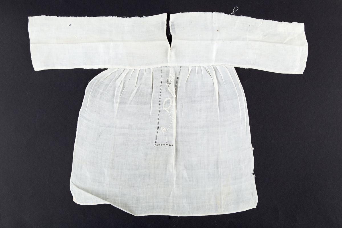 T-formet. Rektangulær smekke. Brettet linning med splitt. Brodert med rankebroderi innrammet av hullsøm.