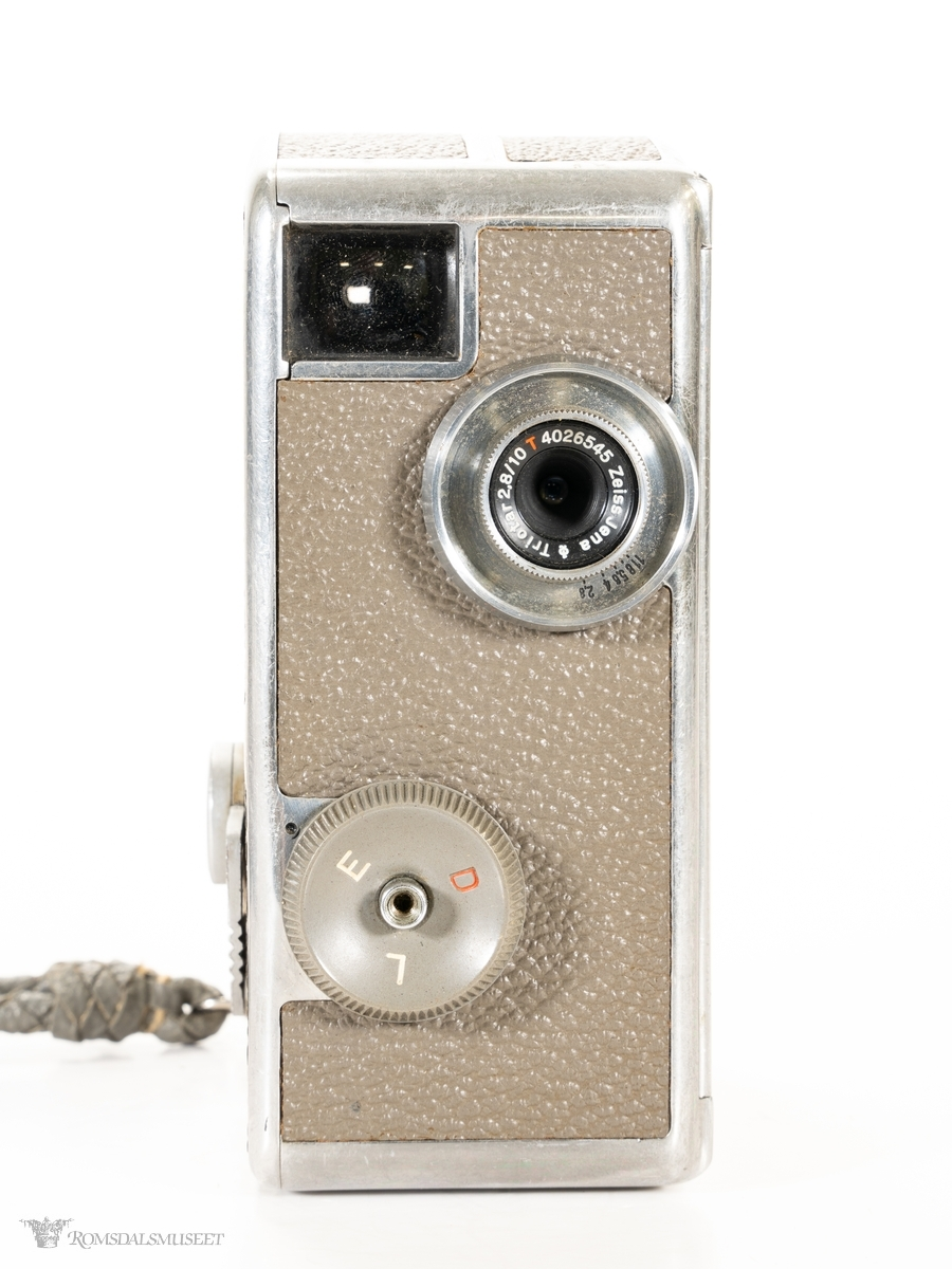 Rektangulært 8 mm filmkamera i metall kledd med nylonbelegg, med avrundet topp. Søker, indikatorvindu for filmlengde og åpningsknapp bak, og linse og velger for filmmetode i front. Hengslet opptrekkshendel på høyre side. Bæreveske i kunstskinn med glidelås og skulderem av lær.