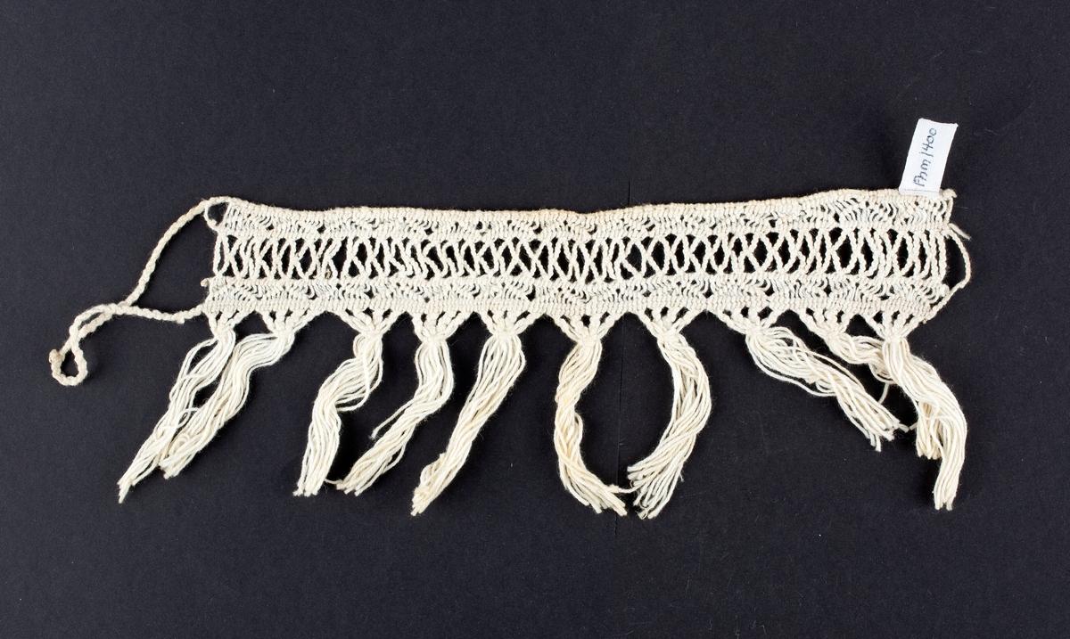 Antakelig gardinholder, utført i en knytte-teknikk. Kort og lang hempe. grynser. Oppført i gammel inntaksprotokoll som hekleprøve