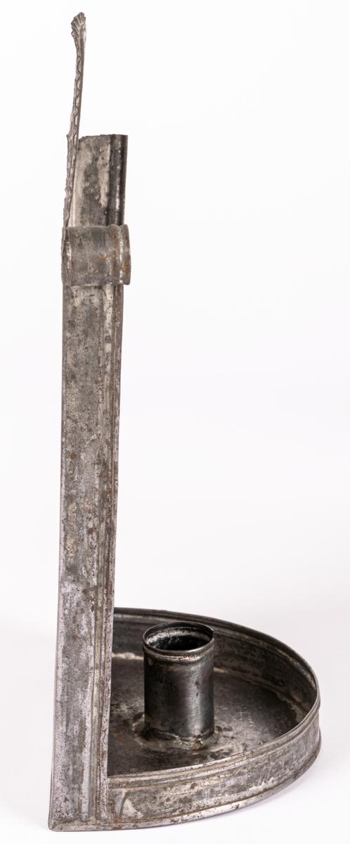 Ljushållare av plåt, halvrund upptill, rundad bricka nertill med ljushållaren. Att fästa på vägg.