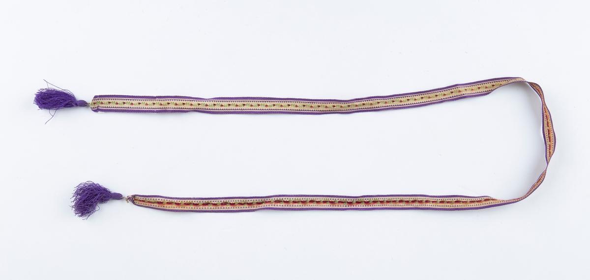 Silkebånd. Smalt. Dusk i endene. Gulhvit bunn. Smal blomst og bladbord i midten, rød og grønn. Violette sidestriper. Violette dusker.