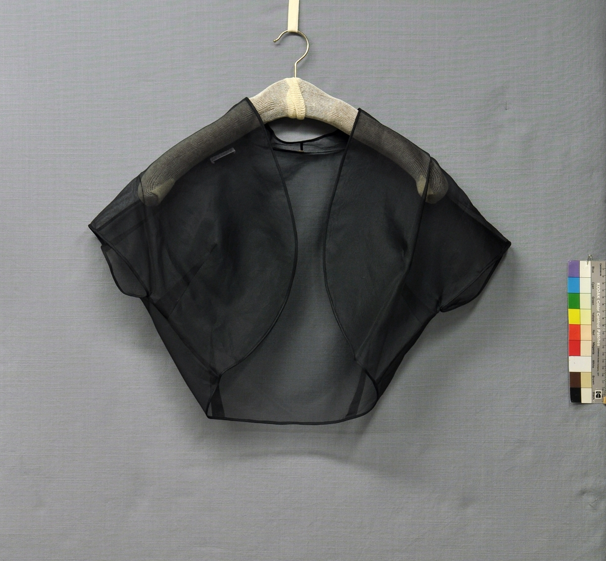 Aftonklänning och skärp i svart sidenorganza med jacka och underkjol. Klänning (BM63901:1). Avskuren i midjan. Baddräktsliv med påsydd dubbelvikt kant, smockrynkad framtill. Spröt i byst- och sidsömmar. Livet fodrat med svart viskostaft. Rundskuren solfjädersplisserad kjol, blixtlås i vänster sida. Skärp med tygklätt spänne. Jacka (BM63901:2). Bolerojacka. Framsidan med rundskuren kant och 2 bystinsnitt. Baksidan helskuren med 2 midjeinsnitt. Ståkrage bak, skuren i ett med framstycket. Holkärm. Rullfållad med vändsydda sömmar. Underkjol (BM63901:3) av 2 våder svart viskostaft med rynkad volang nedtill. 25 mm bred linning, knäppt med 1 knapp. 1 midjeinsnitt i var sida. Storlek 42.