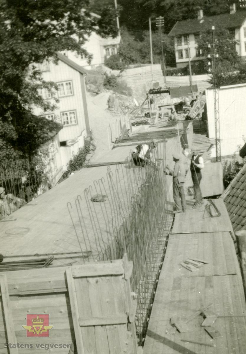 """Østerklev bru i sentrum av Tvedestrand. Forskaling av brudekket, støping anno 1930.  Plassbygget jf. bildene NVM 09-F-00833, NVM 09-F-00859 t.o.m. 00864. Tillegg til: NVM 09-F-01478 og 01479.  Følg pilen til høyre for å se bildene fra byggingen.  Bildene fra byggingen ved Østerklev bru er registrert enkeltvis. Se Relasjon lenger ned på siden.   Østerklev bru, fv. 411 i Tvedestrand sentrum oppført 1930. Bjelkebru. Lengde 40,43 meter. System: Betong. Spennvidde: 23,3 meter + 14,0 meter. Kjørebane: 4,6 meter. Bredde mellom rekkverk: 5,0 meter. Brudekke: Betong. Belastningsklasse: 2/30. Bygget 1930.  Kilde: Statens vegvesen sitt bruregister """"Brutus."""""""