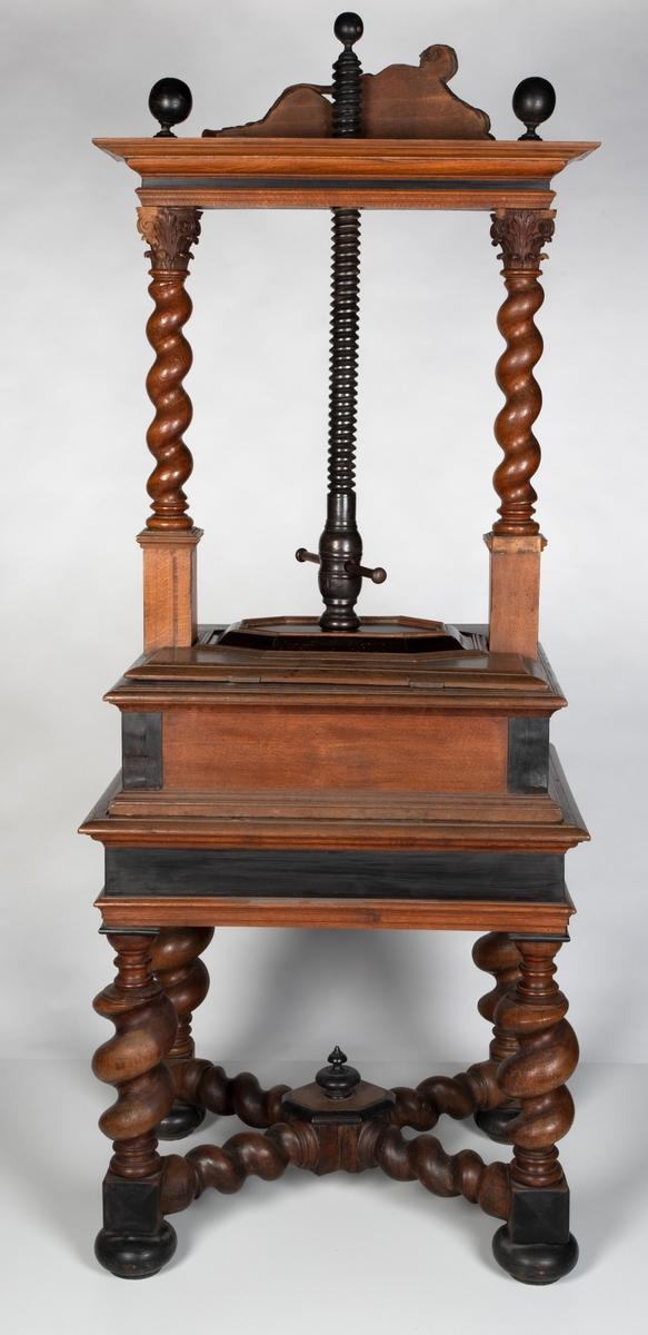 Bordformet lintøypresse i eik og ibenholt. Selve pressen er plassert på bordet mellom to salomonske søyler, som holder opp en gesims med liggende kvinnefigur i klassiske gevanter, omringet av tre kloder. Bordet har to falske skuffer. Under sargen er det utskjæringer som viser akantusranker og blomster. De fire bordbena er dreid som salomonske søyler med kloder som føtter. Bena er forbundet med hverandre i et X-kryss.