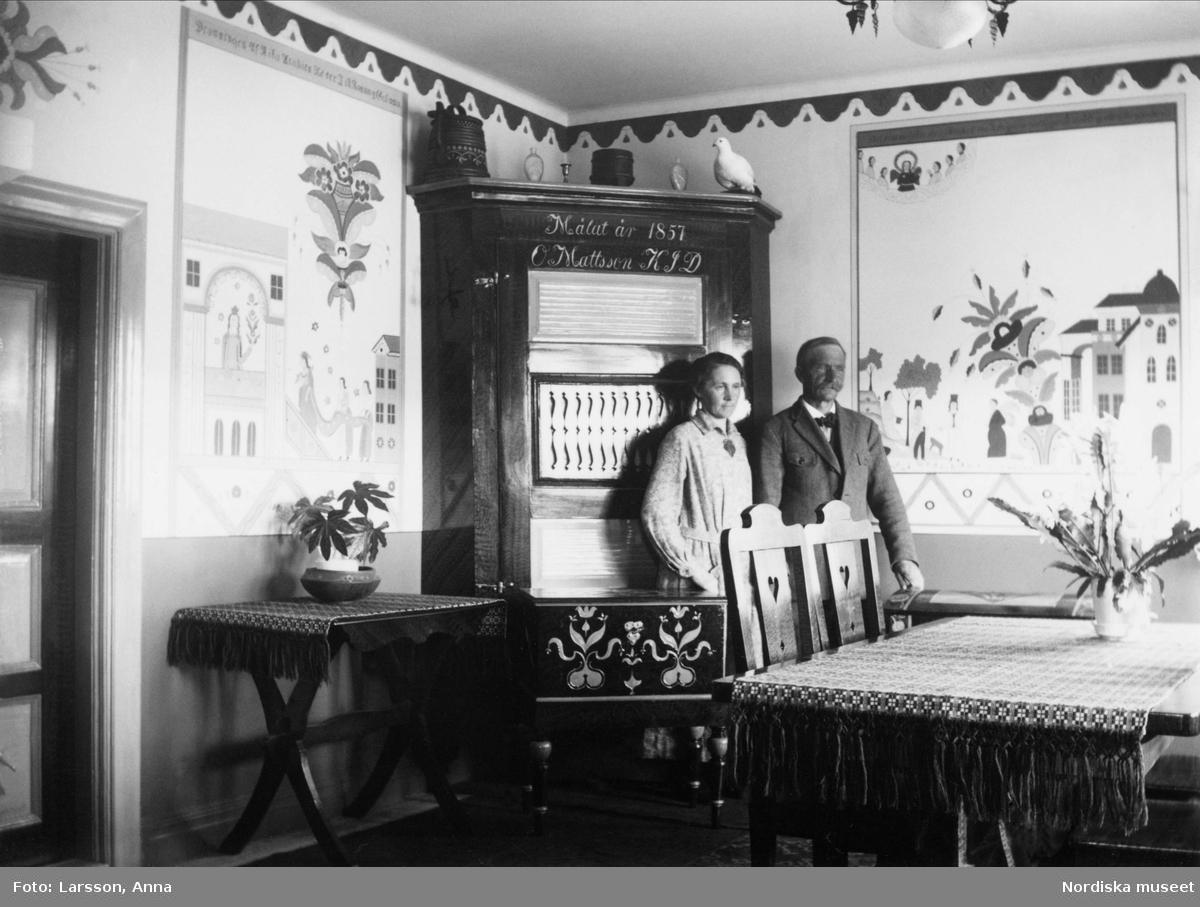 Paret Almgren i sitt hem, stående framför väggskåp med kurbitsmålningar på väggarna