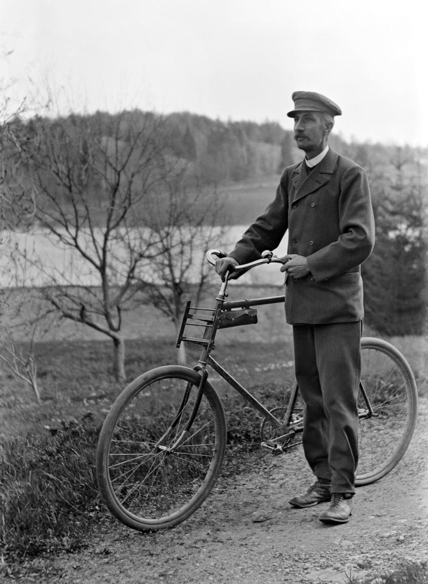 Fotograf Emil Durling poserar med cykel i äppelträdgården vid sitt hem Strömmen i Sankt Anna.