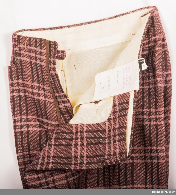 Kavaler herredress, jakke og bukse i lilla rutete tøy. Lilla syntetisk silkefor. Jakka har skulderputer, klaff på lommene, 2 splitter bak og store slag på kragen.  Den er knept med 2 knapper midt framme. 1 pynteknapp på hvert erme.