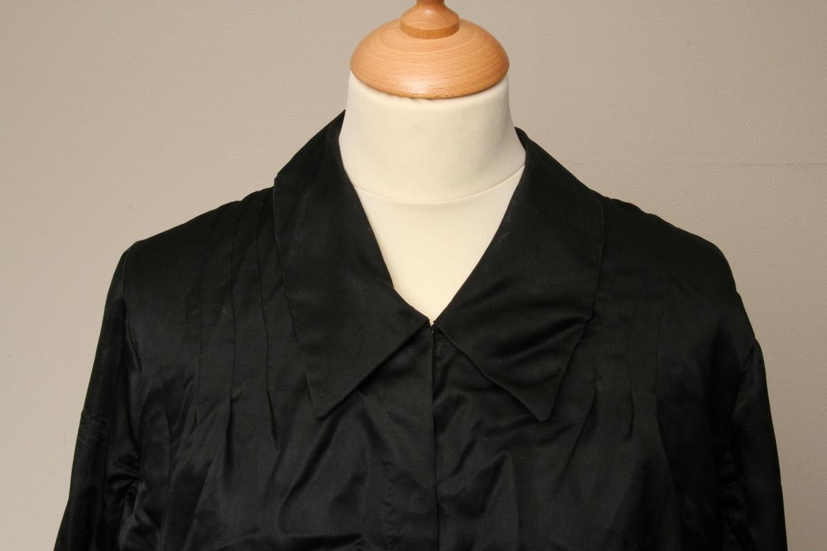 Kjole sydd i svart, blankt silkestoff. Skjørtet er sydd av 5 kapper, festet til et glanset bomullsstoff. Overdelen har en innerdel av det samme bomullsstoffet. Både innerdel og ytterdelen lukkes med trykknapper. Kjolen er i stor størrelse.