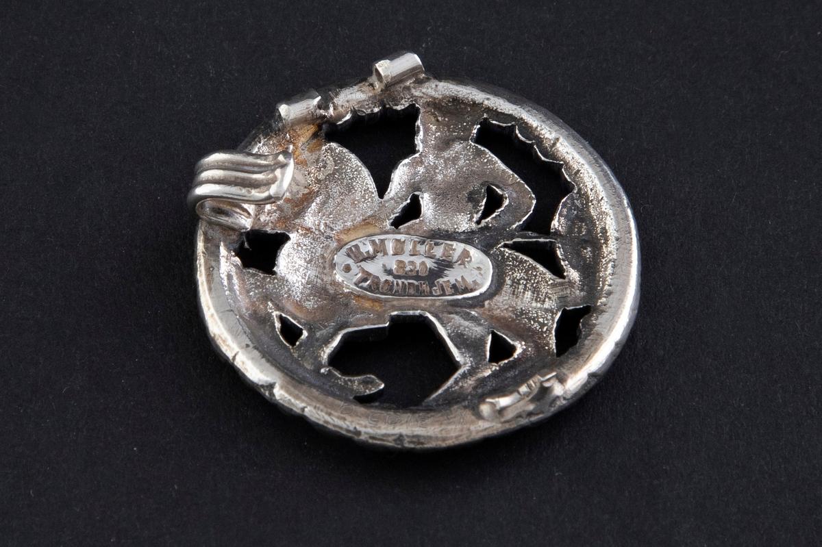To sirkulære spenner i støpt sølv med siselert detaljering. Motivene er hentet fra Gokstadfunnet i 1880.   1) Sirkulær spenne i støpt sølv med siselert detaljering. Fremstilling av en rytter til hest. Gjennombrutt arbeid, omgitt av perlerad. På baksiden er nål og bøyle brutt av.   2) Sirkulær spenne i støpt sølv med siselert detaljering. Fremstilling av et fabeldyr. Gjennombrutt arbeid, omgitt av perlerad. På baksiden er nål og bøyle brutt av.