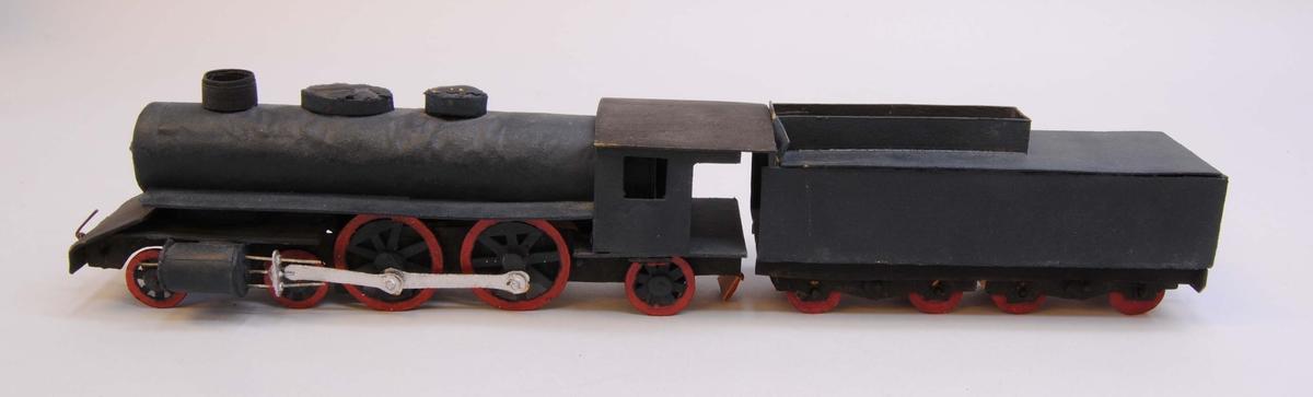 Leksaksånglok (:7) med tender (:8) av huvudmaterialet papp. Delarna är limmade eller sammanfogade med rött lack. Loket har fem hjulpar. Två av dem är av större diameter och kopplade via silvermålade koppelstänger. Hjulen är gjorda av papp och hjulaxlarna av runda träpinnar. Loket är målat i svart och hjulringarna i rött. I lokets främre ände och i tenderns (:7) bakre ände finns koppel av ståltråd. Loket och tendern har varit sammanfogade med ett snöre men lacket som höll det på plats har lossnat från tendern och hänger från ångloket.