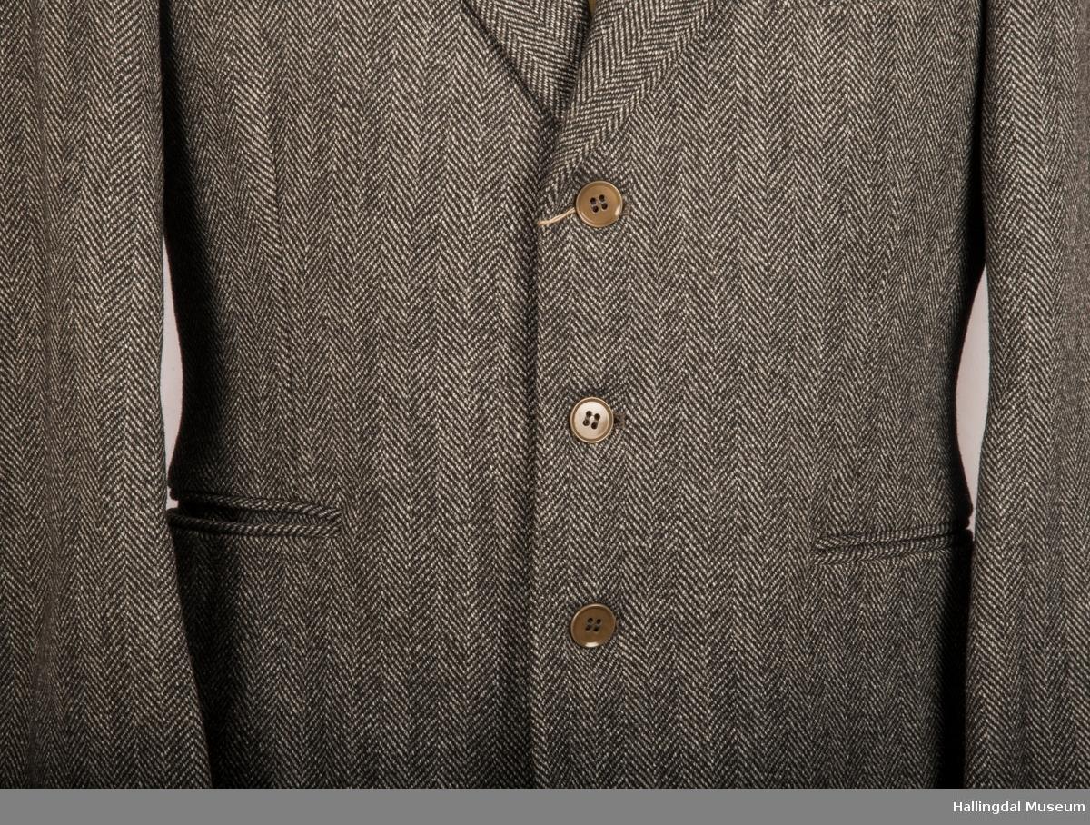 Grå dressjakke i ull med fiskebeinsmønster. Foret med grått syntetisk silkefor.  2 lommer uten klaff, liten brystlomme på venstre side.  En innerlomme på høyre side.  Lukket med 3 brune plastknapper.  3 små plastknapper til pynt på hvert erme.  Uten splitt bak.  Ermene er foret med hvitt stripete syntetisk silkefor.  Vesten mangler.