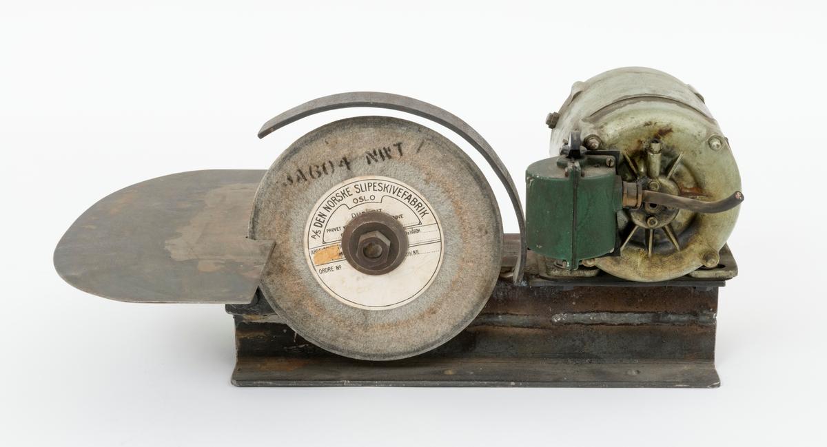 """Slipemaskin, smergelskive, benkslipemaskin, med en skive brukt til formsmergling av sagbladtenner, svanstenner, ved skogskolen på Sønsterud i Åsnes kommune. Slipemaskinens hovedkomponenter er montert på en jernramme. I jernrammas """"fot"""" er det boret fire hull for fastmontering av maskinen med gjennomgående skruer til arbeidsbenk. De tre hovedkomponentene som er montert til jernramma er: elektromotor, smergelskive og anlegg (anleggsbord/plate). Anlegget har tre rette kanter og en buet. Det er utfrest et spor, innhakk, i anleggsplata for smergelskiva. På undersiden av anleggplata, er det påsveiset en brakett for innfesting av anleggsplata i jernramma. En gjennomgående skrue med mutter holder plata fast til jernramma. I jernramma er det utfrest spor, et på hver side, som skruen er tredd gjennom. Ved å løsne skruens mutter, kan anleggets avstand til smergelskiva reguleres.  Smergelskivas aksling som en gjenifinner rett foran anlegget har påmontert en reimskive. (Akslingen til smergelskiva er utstyrt med en smørenippel.) Fra denne reimskiva trekkes det en reim fram til en reimskive på elektromotoren. Reimskiva som hører til elektromotoren og reima som overfører kraft fra elektromotoren til smergelskiva, mangler. Elektromotoren som driver smergelskiva er plassert lengst bak på jernramma. Motoren er skrudd fast til ramma med fire mutterskruer. Elektromotorens fot, feste, har utfreste spor som gjør det mulig å bevege den i lengderetning langs jernramma. Bryter for start og stopp gjenfinnes på ene siden av elektromotoren.  Til beskyttelse av slipeskiva er det påsveiset et 4 centmeter bredt flattjern. Flattjernet strekker seg fra jernramma i en bue over slipeskiva."""