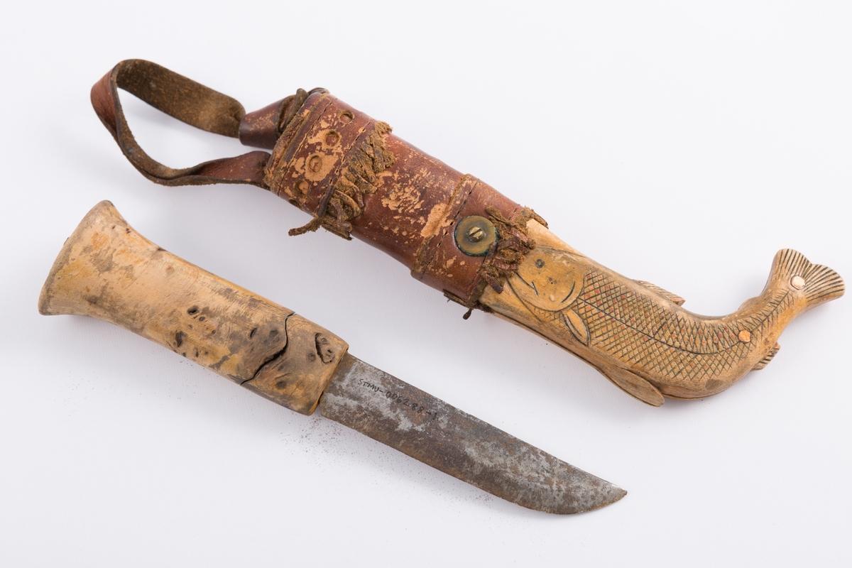 Tollekniv med slire og beltehempe i lær. Skaft tilvirket av lakkert treverk mens slire av lær og treverk. Nederste delen av sliren formet som en fisk.