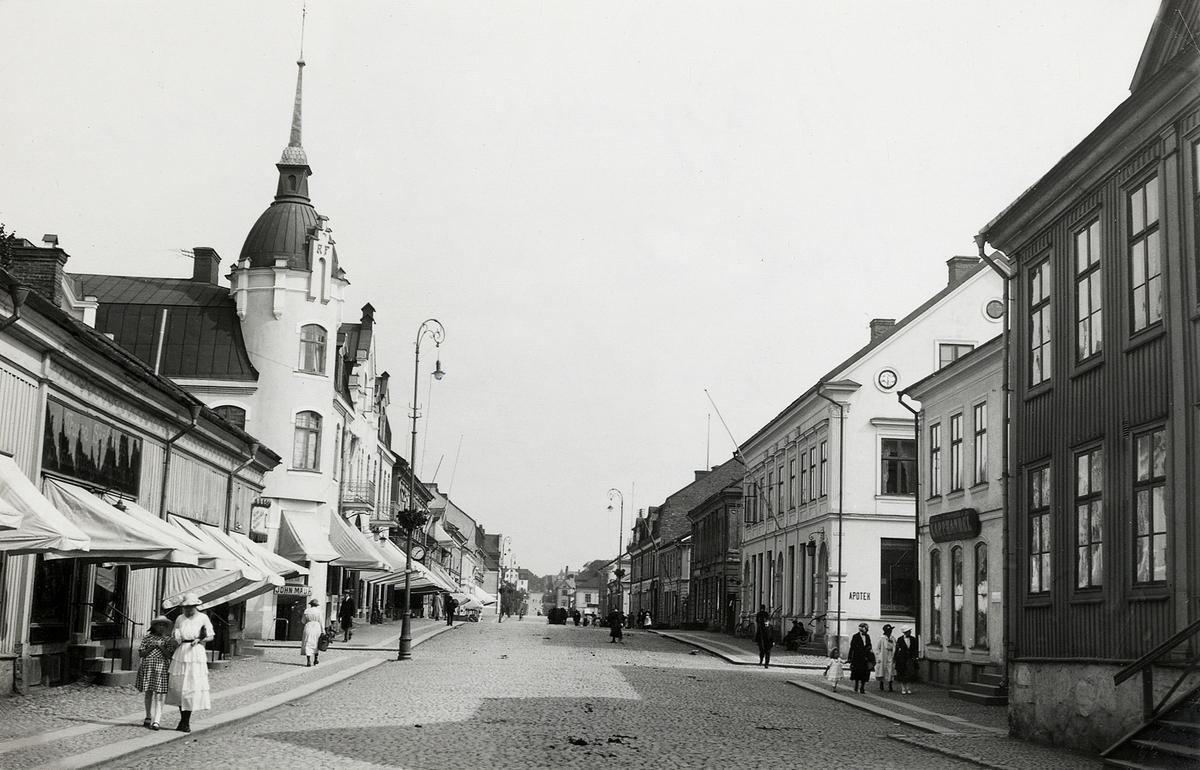 Storgatan vid korsningen mot Bäckgatan, ca 1920-1925, med vy mot öster och Stortorget. Närmast i bild kvarteret Nunnan, följt av kvarteret Klostret med familjen Feuks fastighet, till höger kvarteret Stormen, följt av kvarteret Blenda med apoteket i hörnet.   'Feuk' - Frans Simon Rudolf Feuk (1863-1926), tapetserare m.m., Växjö. Sonen Oscar Feuk (1890-1964), köpman, Växjö.  (Källa: Bl a Folkräkning 1900 och 1910, Växjö stadsfs, Riksarkivet. Sveriges Dödbok 1860-2017)