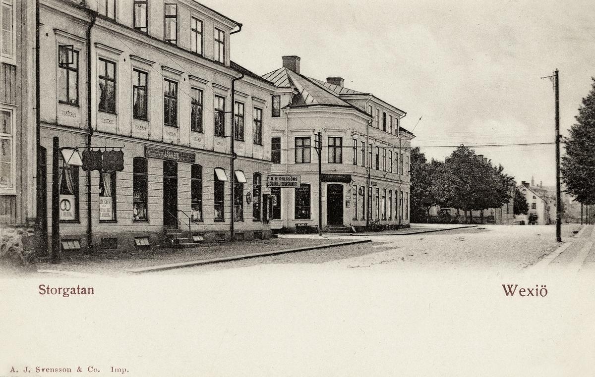 """Storgatan, Växjö ca 1905, nästan i korsningen mot Västergatan, med kvarteret Stormen 1 till vänster, följt av hörnfastigheten  kvarteret Fries 3. I bakgrunden skymtar man Askelyckan m.m.  Vykort.   'J.A. Ahlberg, Bageri"""" - Ido Alfred Johansson Ahlberg (1855-1930), bagarmästare, kv. Stormen 1, Växjö.  'N.H. Ohlssons Cigarr & Tobakshandel' - Nils Håkansson Ohlsson (1867-1909), handlande, kv. Stormen 1.  (Källa: Folkräkning 1900 och 1910, Växjö stadsfs, Riksarkivet. Sveriges Dödbok 1860-2017)"""