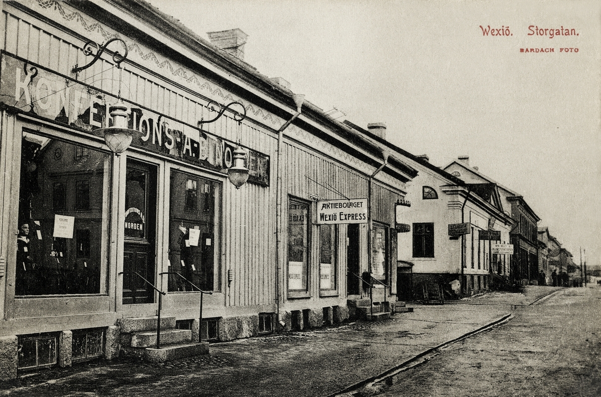 """Storgatan, Växjö, Närmast i bild huset kvarteret Nunnan 3, följt (efter korsningen med Bäckgatan) av husen på kvarteret  Klostret nr 8 och 7.  Vykort.   """"Konfektions AB Norden""""   ? """"Växjö Express"""" - åkeribolag bildat ca 1900 av majorerna Adolf Reuterswärd, Carl Myrin och Erland Hederstierna. (Se Hyltén-Cavallius, Nils, """"Gamla Växjö berättar"""", s. 47-48)."""