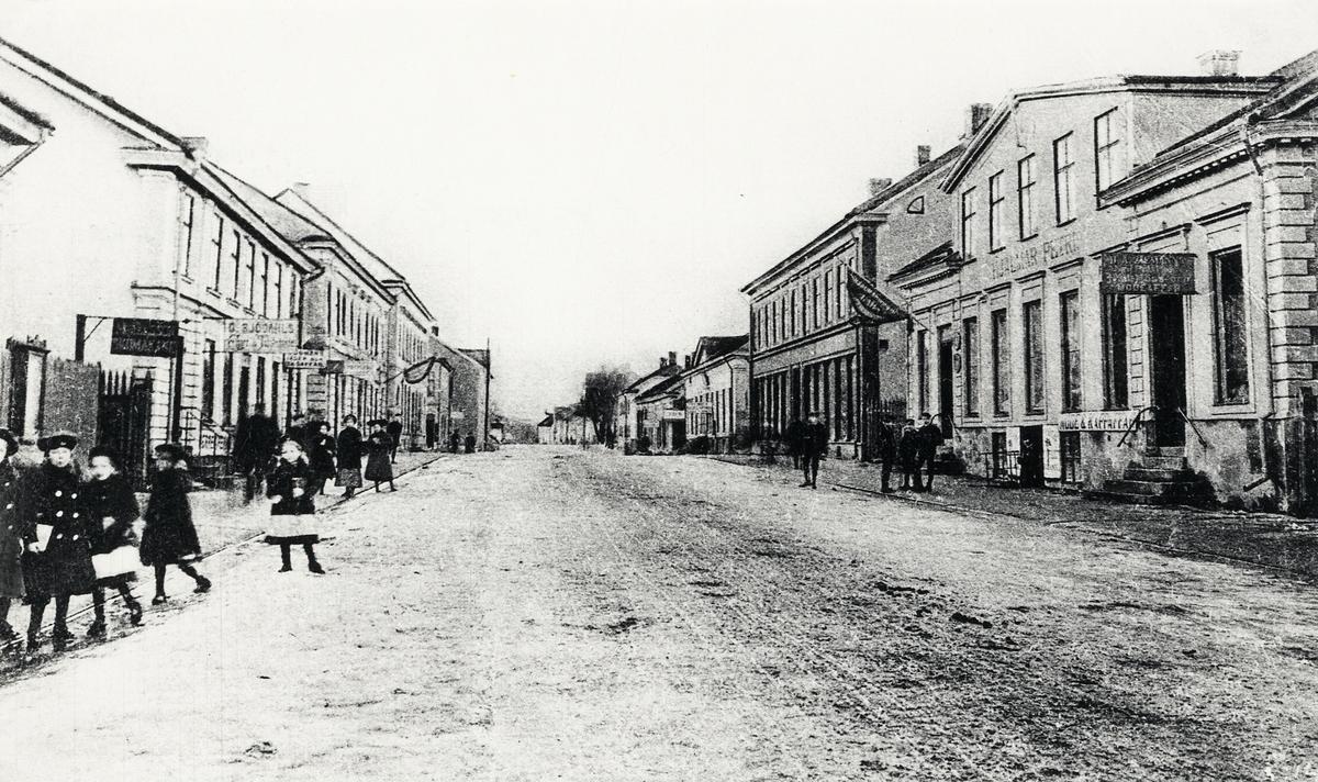 Storgatan, Växjö ca 1905-10, med blick västerut. Till vänster ser man husen i kvarteret Blenda med G. Sjödahls affär m.m. Till höger ser man konsul Hjalmar Petris fastighet på kvarteret Klostret 6, följt av diverse andra hus i kvarteret och i fjärran kvarteret Nunnan.   'G. Sjödahls affär' - Gustaf Wilhelm Sjödahl (1871-1919), handlande, kv. Blenda 3, Växjö.  'Konsul Hjalmar Petri' - Adrian Hjalmar Petri (1848-1932), handlande, vicekonsul m.m., kv. Klostret nr 6. (Källa: Bl a Folkräkning 1900, 1910 och 1930, Växjö stadsfs, Riksarkivet. Sveriges Dödbok 1860-2017)