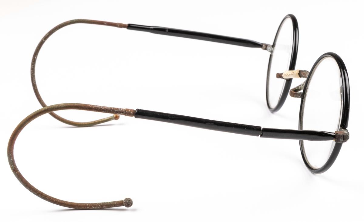 Glasögon, med svarta bågar.