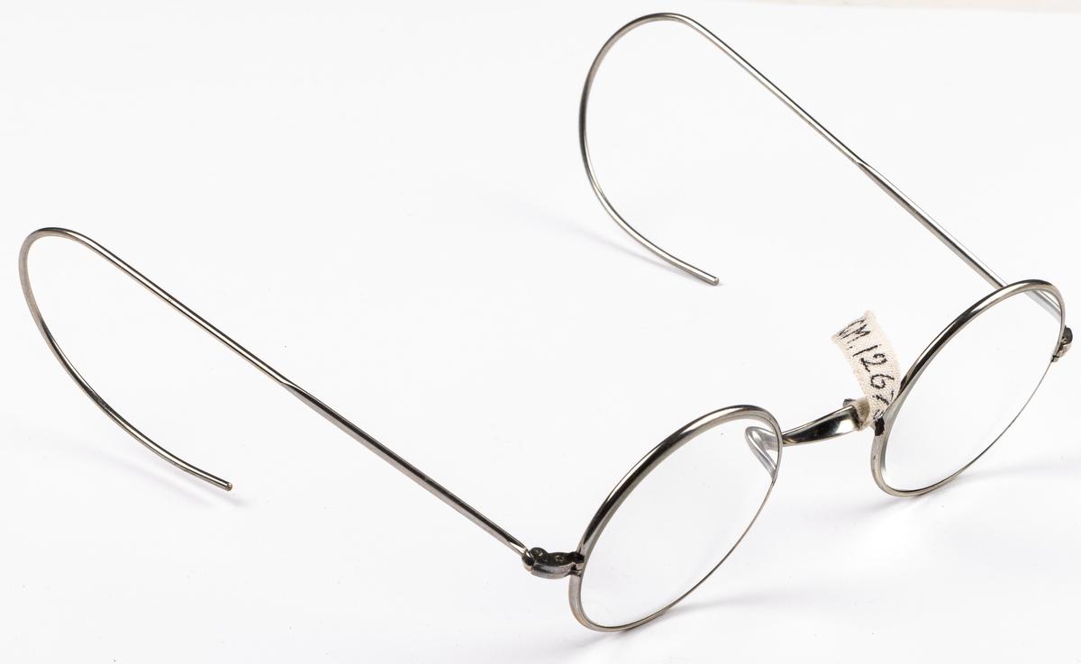 Kat. kort: Glasögon, med nickelbågar, i svart fodral. Från A. Palmér Ur o. Optik, Bollnäs.
