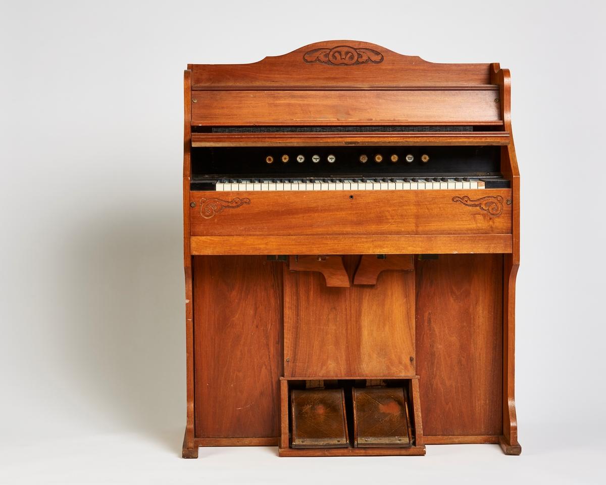 Orgel med 10 tunger og to trøpedaler. Låsbart lokk og bakplate er løst. På hver side og øverst har det utskåret dekor av akantus. Orgelet er lakkert.