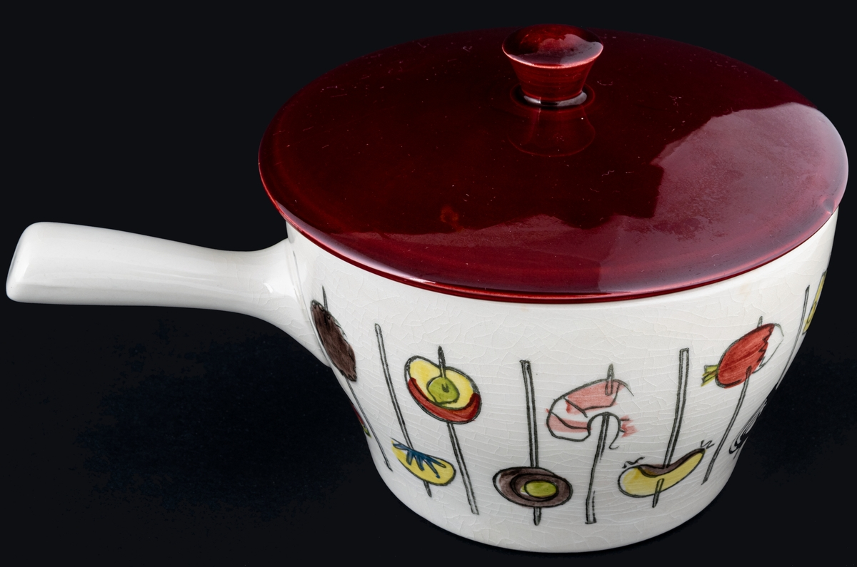 Gryta med handtag med dekor Cocktail, rött lock. Stämpeldekor med handmålning i flera färger. Formpressad. Formgivare Berit Ternell för Gefle Porslinsfabrik 1959. Stämplad undertill med logotypen tre ugnar samt UE GEFLE.