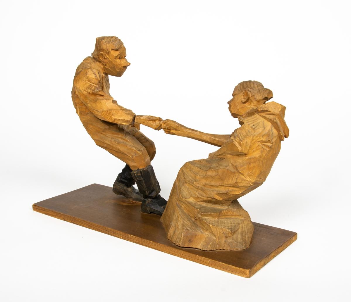 """Skulptur i trä av Döderhultarn. Skulpturen föreställer två figurer, en man och en hustru i en dragkamp, så kallad """"fingerkrok"""". På figurens fotplatta finns en dedikation: """"Från Axel Petersson till Flygaren å vännen Rodéhn 2/9 1919. En ringa gärd af tacksamhet för tvänne i allo förstklassiga """"himmelsfärder"""". Länge lefve Br Rodéhn!!! D.S"""". Jämte dedikationen finns konstnärens signatur synlig i form av en stämpel."""