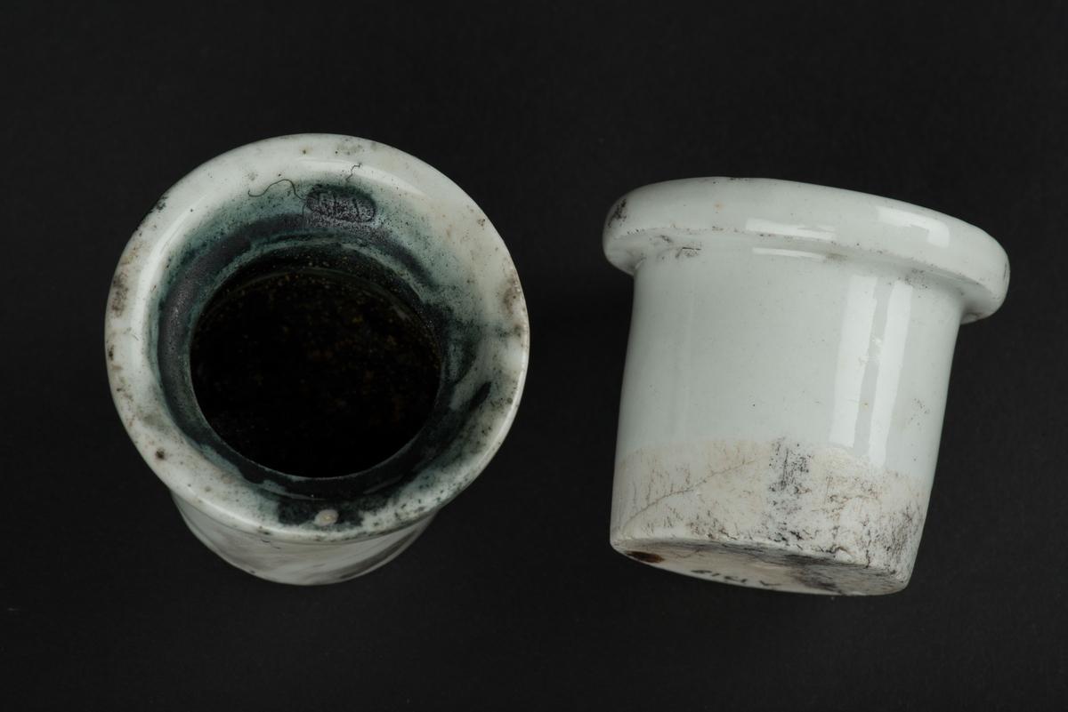 Delbart bläckställ av porslin. Bläckstället föreställer en vilstol där det halvligger en kvinna med ett barn i famnen och ett barn stående vid fotändan.  Stället är i två delar och inuti finns två uttag för de lösa behållarna för bläck och sand. Sanddosan är gjord i ett stycke och har en perforerad ovansida. Bläckinsatsen innehåller torkat pulvriserat bläck.