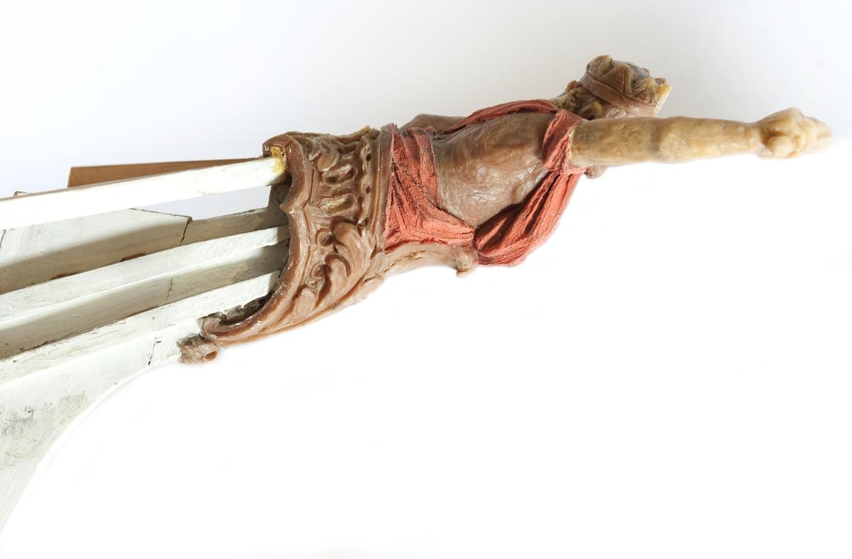 Galjonsbild, modell i gul vax föreställande turuma LODBROKs galjon. Halv mansfigur infattad i akantusbladverk. Huvud med nordmannakrona. Vänster arm utmed sidan, hållande ett  svärd (saknas). Höger arm riktad uppåt. Avslagen. Rödfärgad mantel virad om kroppen och högra armen. Monterad  till stävkonstruktion av vitmålat trä med delar av galjonskorg.