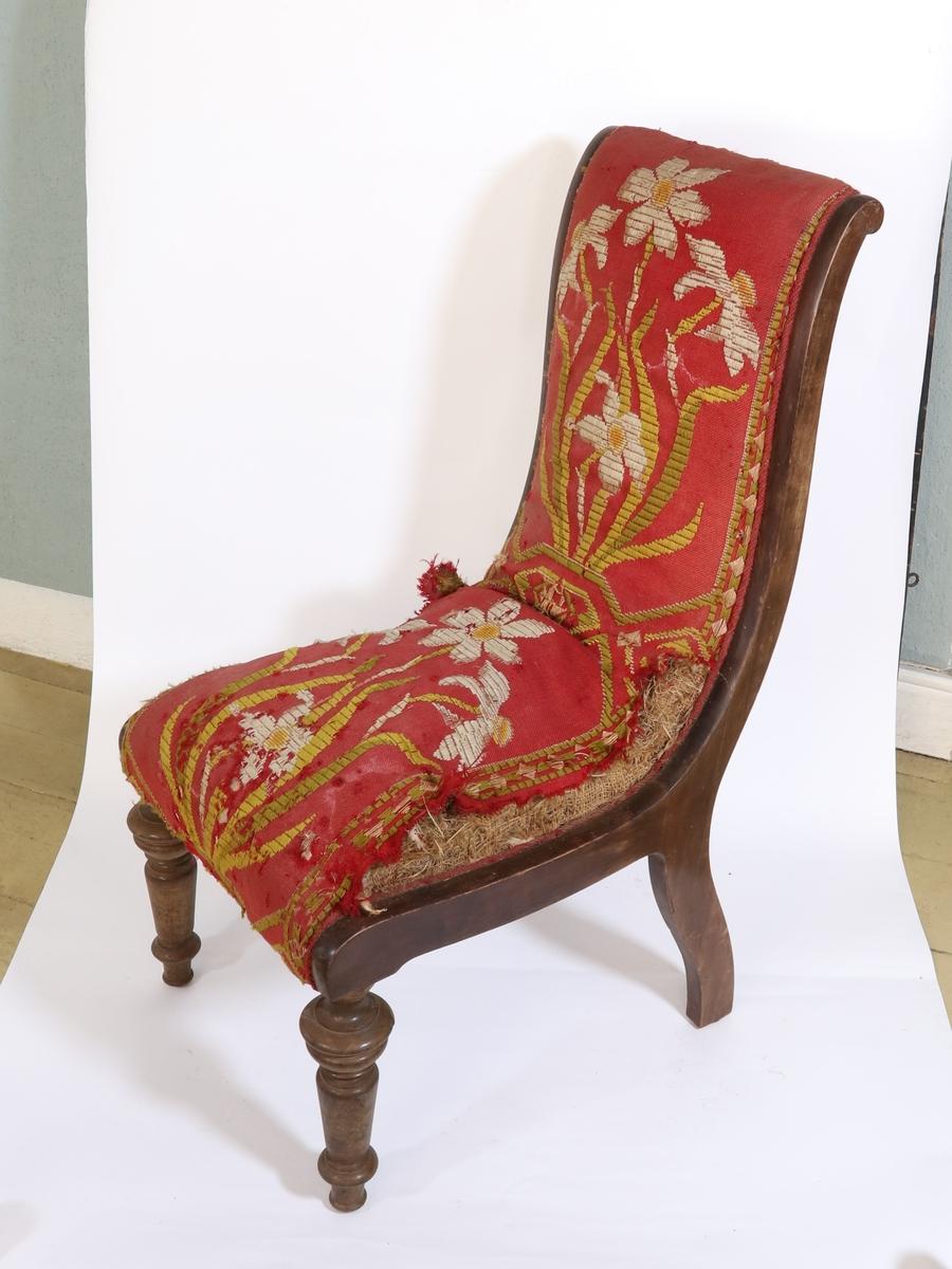 Stoler av massivt tre med polstring på sete og rygg. Polstringen består blanet annet av halm, og er trukket med rødt stoff vevd med hvite blomster og grønne stilker. Fremre stolben er dreid.